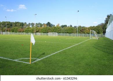 Green empty football field in summer with white flag