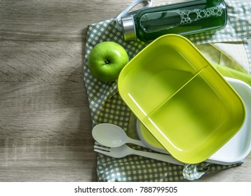 green empty lunch box wrapped  on wooden table , top view or overhead shot , green food concept