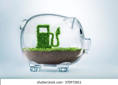 Green energy concept with grass growing in shape of fuel pump inside transparent piggy bank