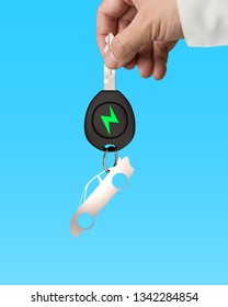 Green energy electric car and lightweight high strength speed concept. Businessman hand holding electric car key with sheet metal keyring in sports car shape, isolated on blue background.