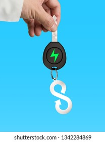 Green energy electric car, lightweight high strength speed and circular economy concept. Businessman hand holding electric car key with sheet metal keyring of infinity arrow symbol, blue background.