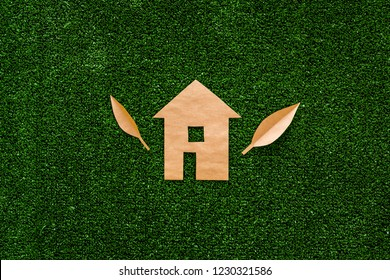 Green energy for home concept. Care for environment. House cutout made of craft paper on green grass background top view space for text