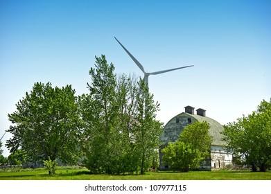 Green Energy and Old Farm Barn Between Threes. Modern Wind Turbine in Background.