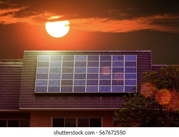 Green energy of solar cell panel on house roof in sunset sky and lens flare