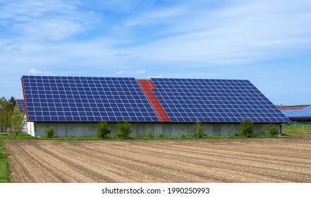 Grüne Energie mit Sonnenkollektoren auf dem Dach eines landwirtschaftlichen Gebäudes