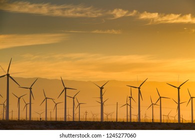 Green energy of wind power being harvested during the golden hour with a warm hued sky from a rising sun behind distant mountains.