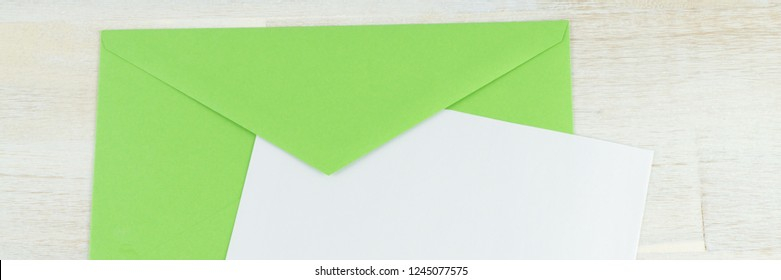 Green envelope with blank letter, banner and wooden background