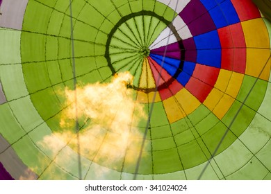 Green envelope of the hot air balloon with yellow, blue, orange, white and violet strips with a fire from a burner