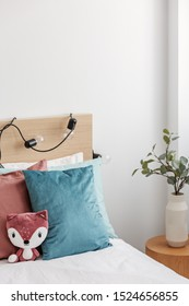 Green eucalyptus in stylish vase on wooden nightstand next to single bed with toy, and blue and red bedding