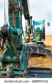 Green Excavator on the territory of beginning construction