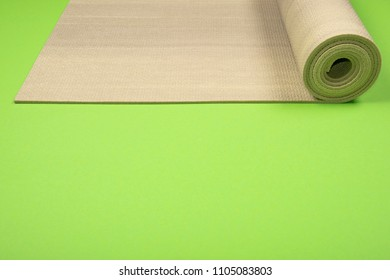 Green exercise mat on green background with copyspace. Yoga practice, physical workout, pilates or fitness concept.