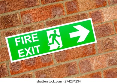 Green exit emergency sign with white lettering on a brick wall background