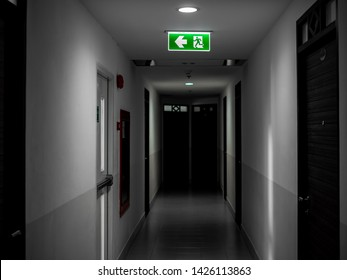 Green exit fire sign hanging on ceiling on dark mysterious corridor in building near fire exit door. Door room perspective in lonely quiet building with light on black and white style vertical style.