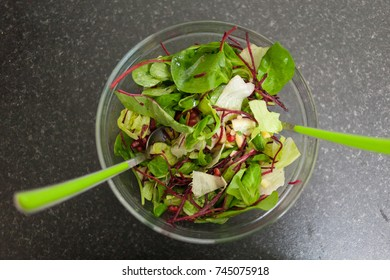 Green exotic salad in a glass pot on dark background.