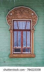 Green facade of a wooden house. One window  decorated brown wood carving frame with mermaid. Snowfall. Russian folk style. Front view close up.