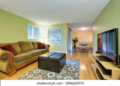 Green family room with adjoining dining area, furnished with a black leather ottoman placed on floral pattern rug facing green sofa. Northwest, USA
