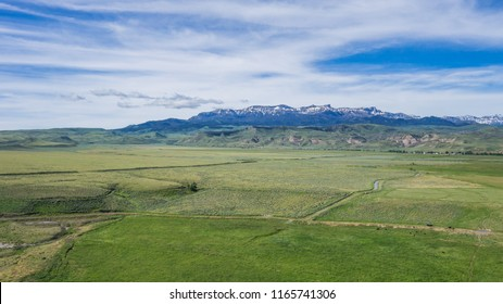 Green farm fields lay below a snow-capped mountain range in the western states of America.