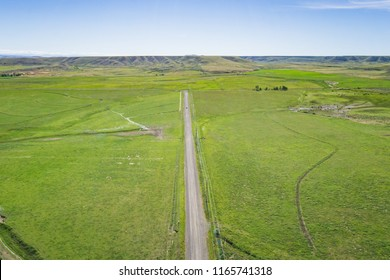 Green farm fields line a gravel road in the flat lands of America's great plains.
