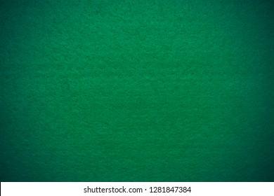 Green felt background with vignette, closeup