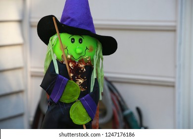 Green Felt Witch Halloween Decoration with Black Eyes Wood Broom Blue Cape and Hat with Shiny Bronze Ruffles against White Wall of Victorian-Style Townhome in Burke, Virginia