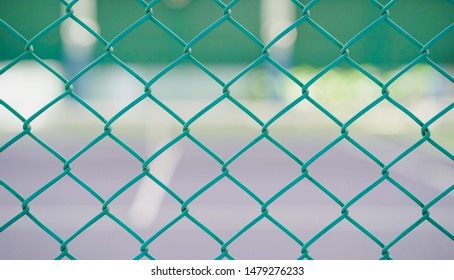 green fence of indoor tennis court with blurred court as background