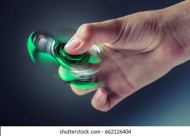 Green fidget spinner in a girl hand.