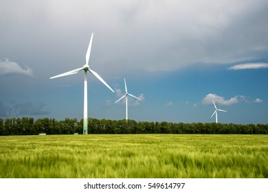 Green field of barley and wind turbines generating electricity
