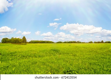 Green field, blue sky, bright clouds and sun