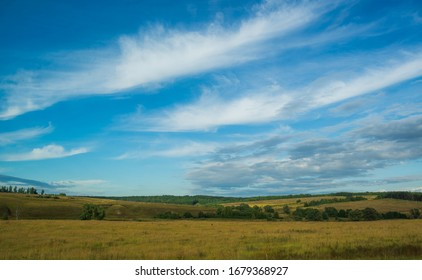 the green field and blue sky with clouds