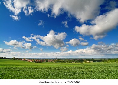 green field, fluffy white cumulus and blue sky