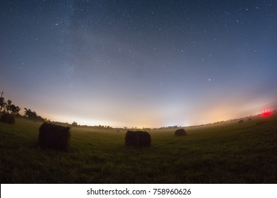 Green field with haystacks at the starry night