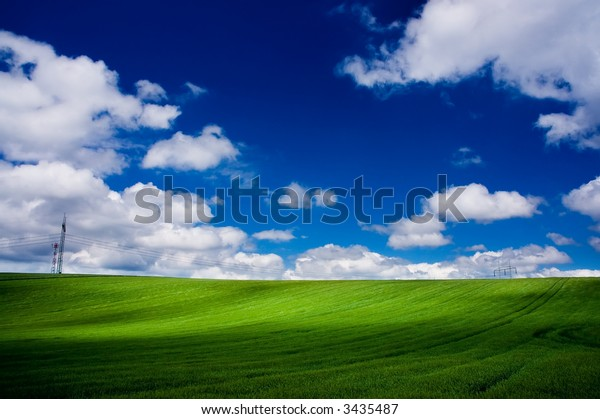Green field - Landscape green grass, blue sky and white clouds, plus high voltage line