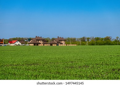 Green field and low rise individual housing residential neighborhood. Belgorod city, Southwest district, Russia. Suburban landscape.