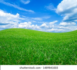 Green field and meadows against the blue sky with white clouds.