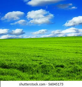 green field over blue sky with clouds