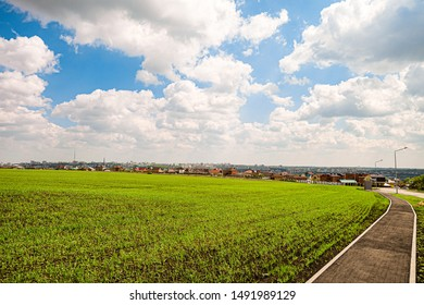 Green field slope and city skyline in the background. Belgorod city, Southwest 2.1 district, Russia.