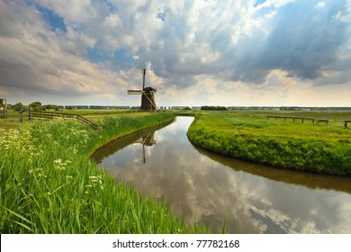 Green field with a windmill in summer