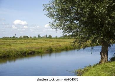 Green fields, creek and windmills in famous Zaanse Schans village near Amsterdam, Netherlands