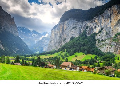 Green fields and famous stunning touristic town with high cliffs in background,Lauterbrunnen,Bernese Oberland,Switzerland,Europe