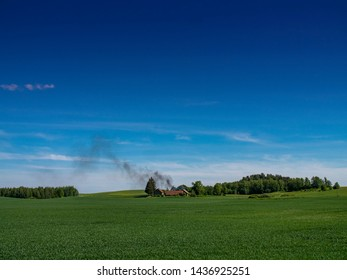 Green Fields with homestead and smoke in the distance