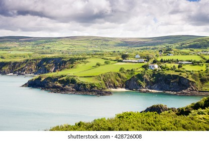 Green fields lead down to cliffs and sea at Newport Bay, seen from Dinas Head in the Pembrokeshire Coast National Park, Wales.