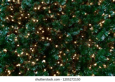 Green fir branches with gold garlands. Christmas homogeneous background.