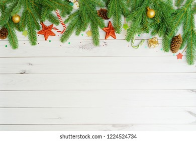 Green Fir tree branches with pine cones, lollipops, toy snowman's, gift box, gold ball on light wooden background. Christmas concept.