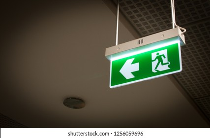 Green fire escape sign hanging from ceiling with arrow direction. Emergency exit symbol.