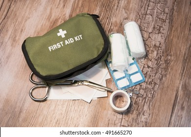 Green first aid kit on wooden background. Bandages, scissors and medicines