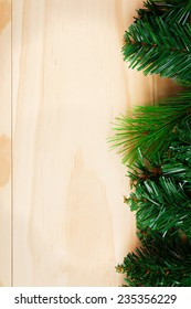 Green fir-tree branches on wooden background. Space for text