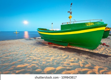 Green fishing boat on the beach of Baltic sea, Poland