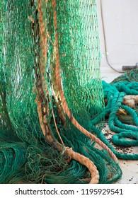 Green fishing trawl net henging on a trawler boat deck
