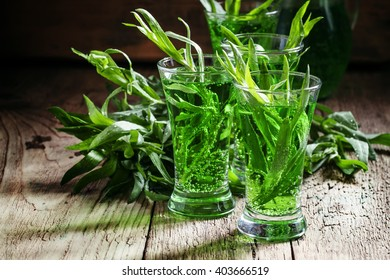 Green fizzy drink with tarragon, vintage wooden background, selective focus