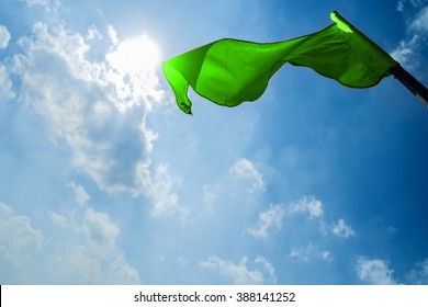 Green flag on a background of the dark blue sky with clouds.